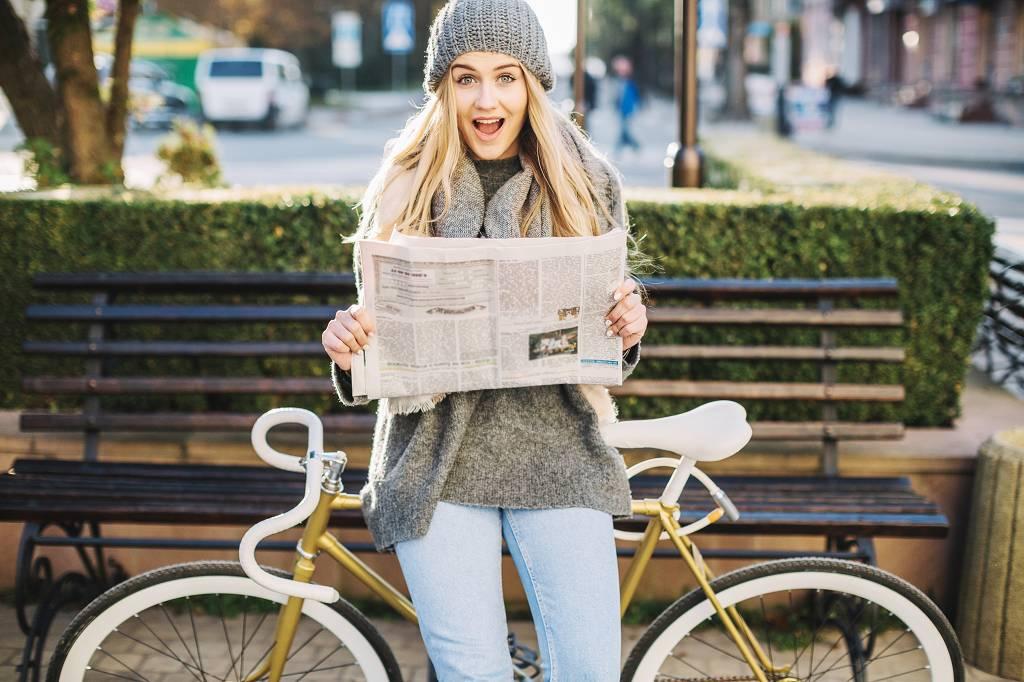 Das Foto zeigt eine junge Frau vor einer Parkbank, die eine Zeitung in der Hand hält. Sie schaut mit einem überraschten Gesichtsausdruck in die Kamera und lehnt sich dabei auf ein Fahrrad hinter ihr.