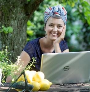Franzi sitzt an einem Tisch im Garten. Vor ihr steht ein aufgeklappter Laptop. Sie trägt ein Sommerkleid, trägt einen Turban und lächelt in die Kamera. Ihren Kopf hat sie auf einen Arm gestützt.