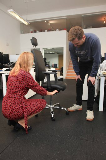 Female health professional adjusting the height of an office chair whilst the office worker watches during a health ergonomics assessment in the workplace.