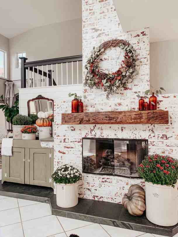 diy faux fireplace decorated with pumpkins and mums for fall