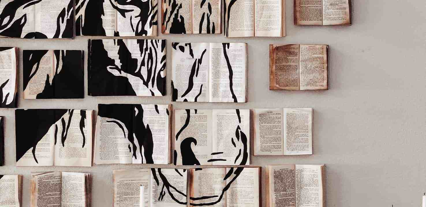 vintage farmhouse inspired living room with chalk painted white buffet, and diy aged book art installation with hose sketch painted on the books