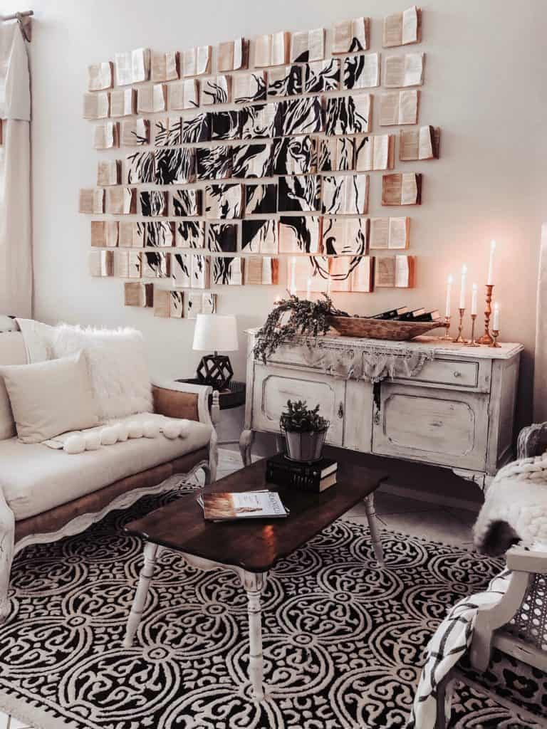 vintage farmhouse living room with balcn and white rug, chalk painted sideboard, and diy book wall art installation with horse painted on the books
