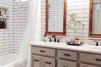 modenr farmhouse bathroom featuring subway tile, wood mirros, and instant granite countertops
