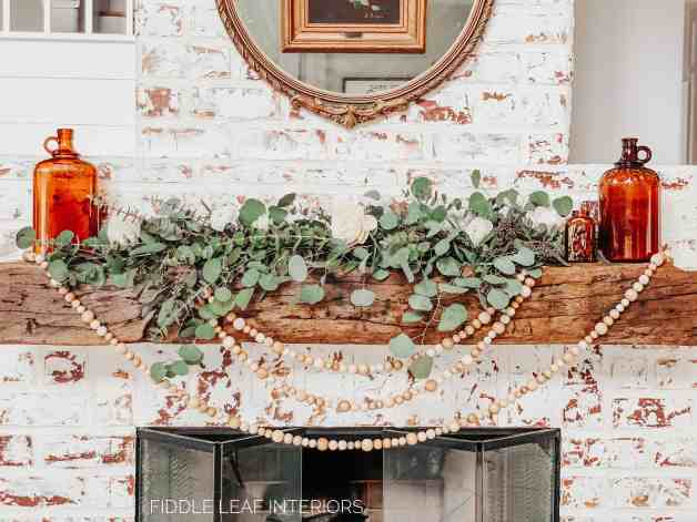 spring mantel styling with fresh eucalyptus, wood beads, and vintage amber bottles on each end