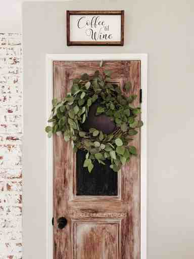 eucalyptus wreath on faux wood door with chalkboard
