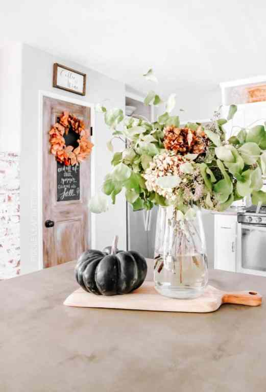 black mud paint pumpkin and glas vase filled with hydrangeas and eucalyptus sitting on wood cutting board on a concrete kitchen counter, with faux wood door in the background that has an orange leaf wreath hanging on it