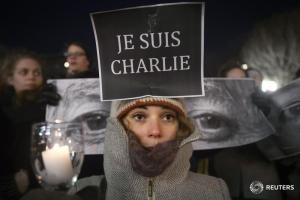 """Amandine Marbach from Strasbourg, France, takes part in a vigil to pay tribute to the victims of a shooting, by gunmen at the offices of weekly satirical magazine Charlie Hebdo in Paris, in the Manhattan borough of New York January 7, 2015. Hooded gunmen stormed the Paris offices of the weekly satirical magazine known for lampooning Islam and other religions, shooting dead at least 12 people, including two police officers, in the worst militant attack on French soil in decades. Sign reads """"I am Charlie"""".    REUTERS/Carlo Allegri   (UNITED STATES - Tags: CIVIL UNREST CRIME LAW TPX IMAGES OF THE DAY) - RTR4KHDZ"""