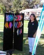 A volunteer standing beside merchandise.