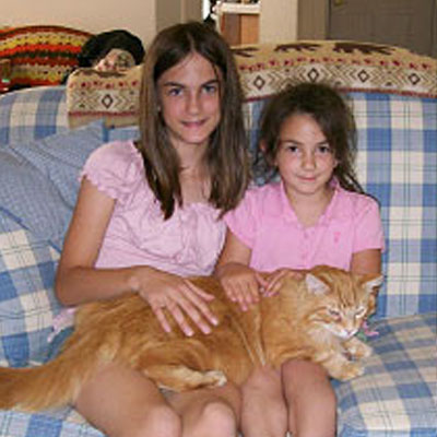 Two young girls with their adopted orange kitty, Elton John