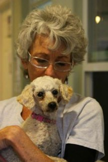 Volunteer Janice Covington holds a small dog.