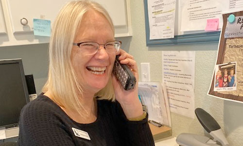 A volunteer answering phone calls for the Community/Cat Assistance Team (CAT)