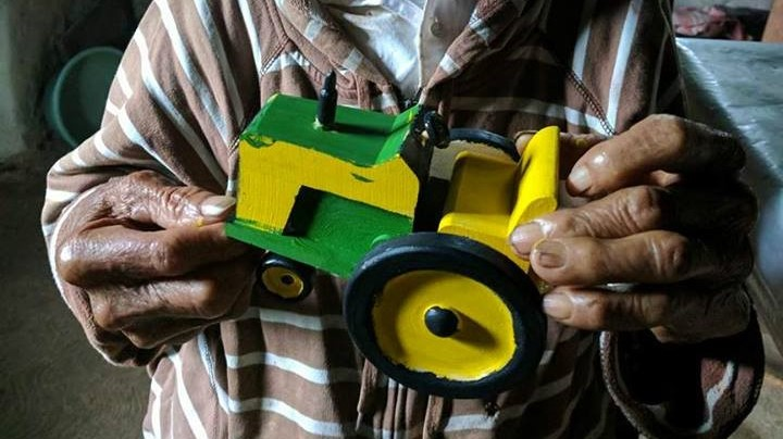 Elderly man painting tractor in Honduras 6