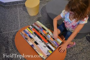 girl looking at art book in Des Moines Art Center