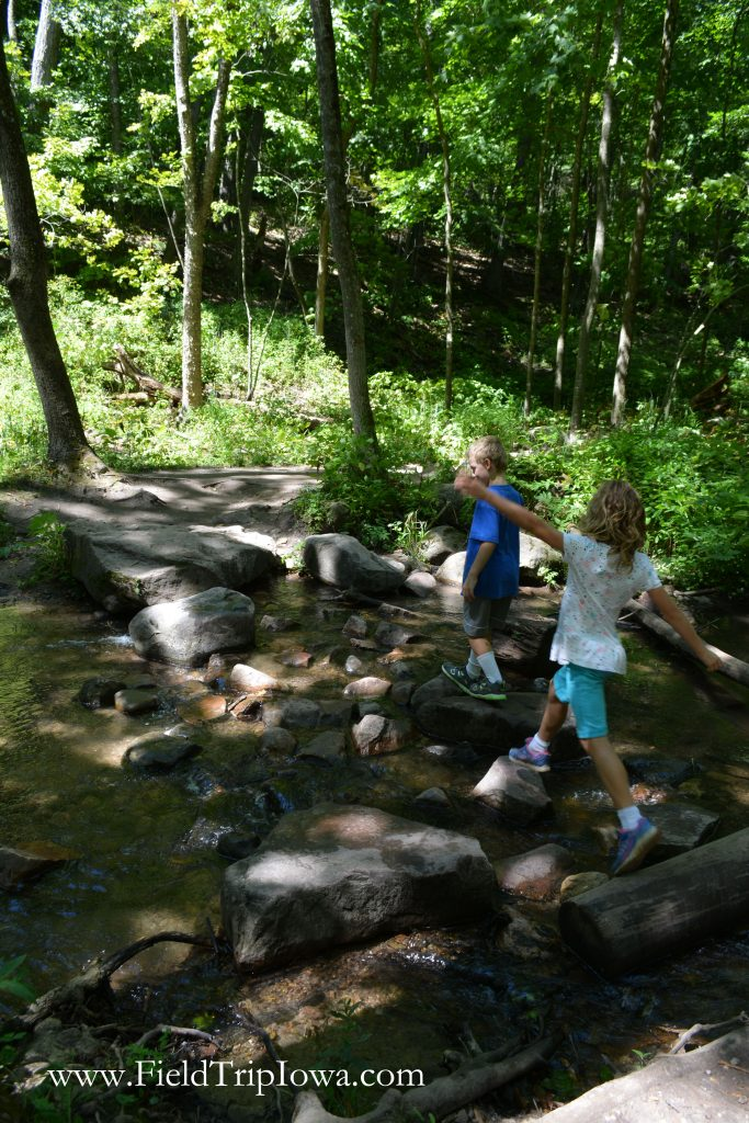 Children have fun skipping across stones at in Parfrey's Glen Natural Area near Devil's Lake Wisconsin