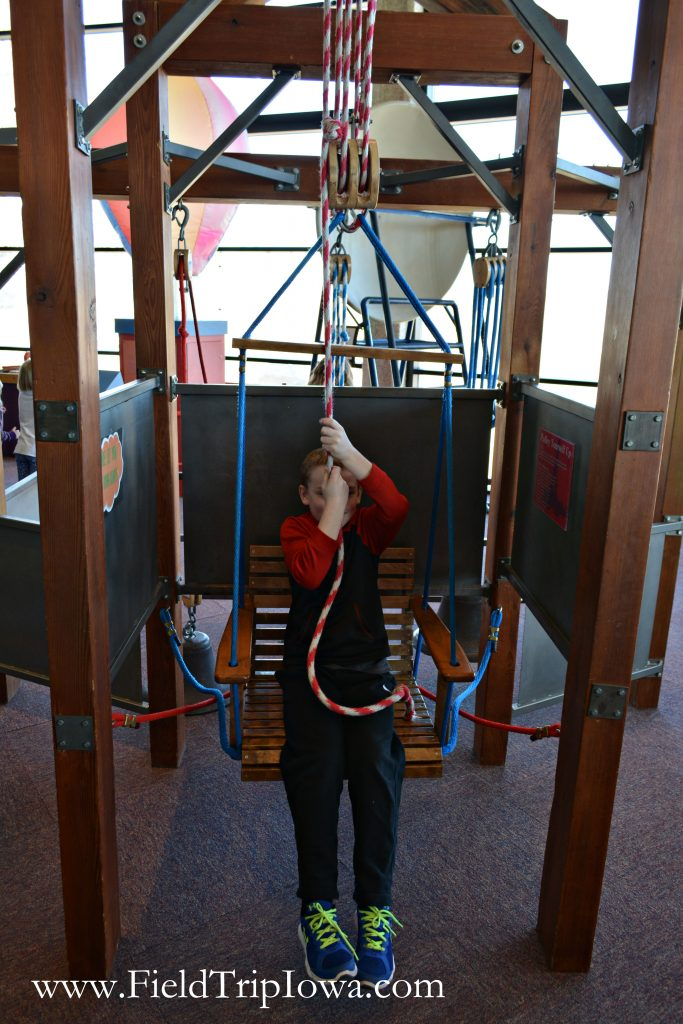 Child uses pully swing at Bluedorn Science Imaginarium in Waterloo Iowa.