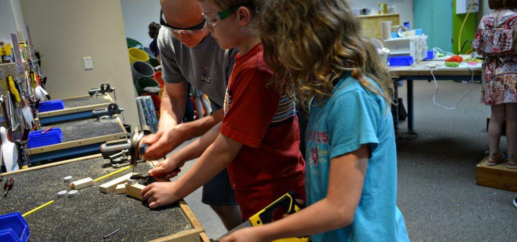 Dad helps children saw in workshop at Family Museum in Daventport