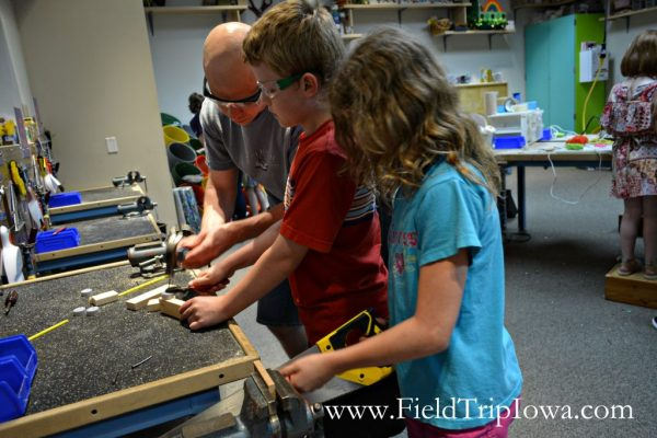 Dad helps children saw in workshop at Family Museum in Daventport