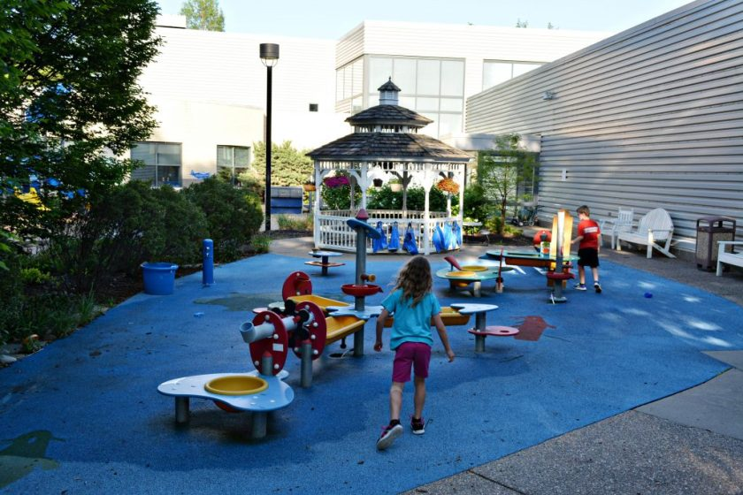 Children run in splash pad area at Family Museum in Daventport