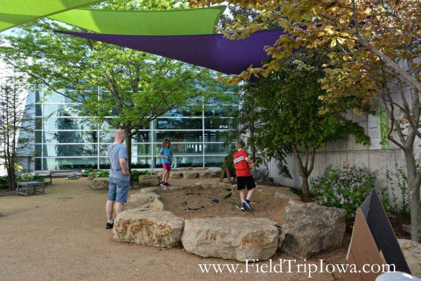 Children dig in dirt outdoors at Putnam Museum in Quad Cities.