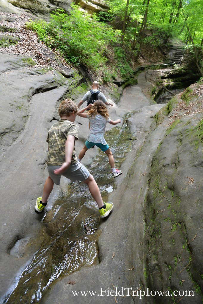 Kids straddling water to leave the French Canyon in Starved Rock State Park, IL
