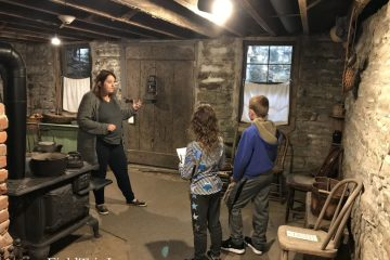 Children get a tour of the basement with dirt floors at the Jordan House in West Des Moines