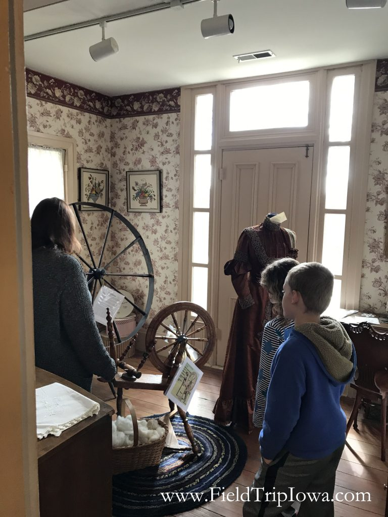 Children view spinning wheel in the sewing room at the Jordan House in West Des Moines