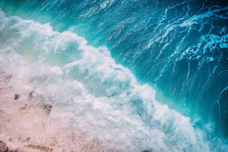 Aerial photo of ocean waves along beach.