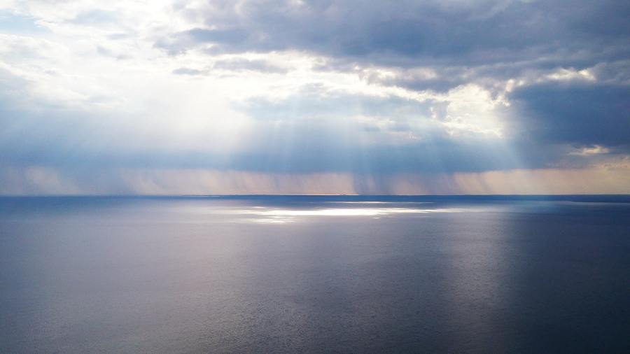 light shining through clouds in open sea