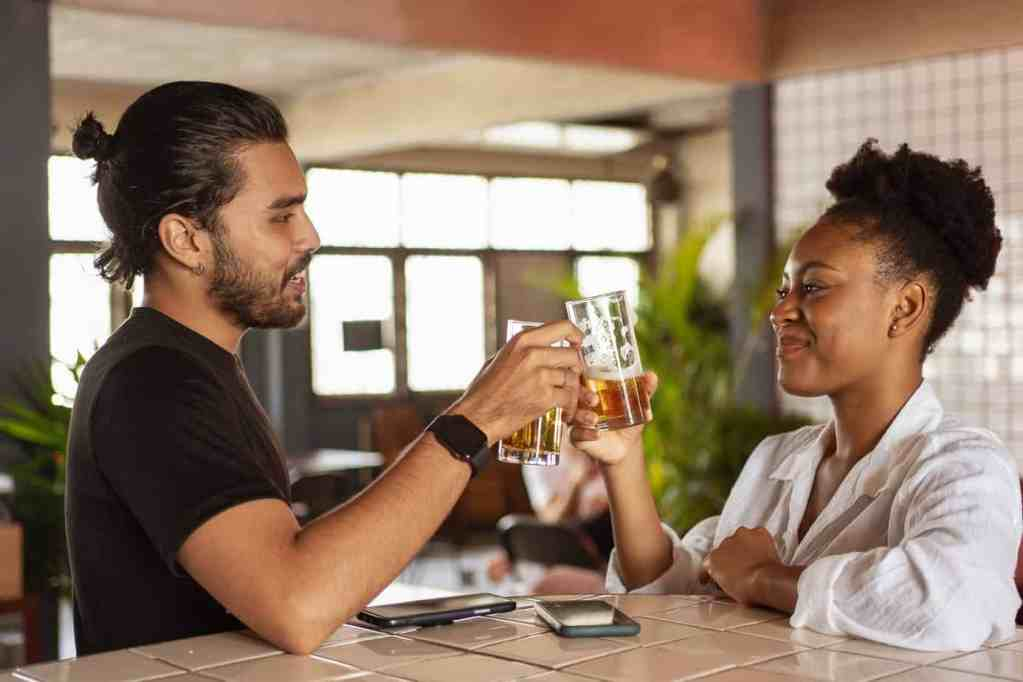 man and woman clinking two drinking glasses with beer