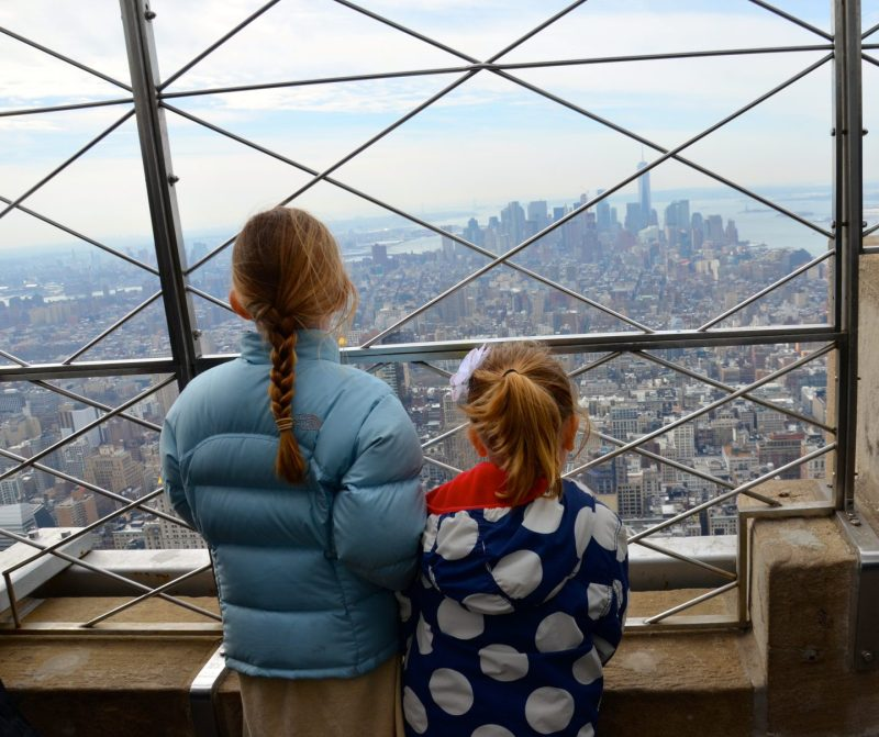 Kids looking out onto Manhattan from the top of the Empire State Building