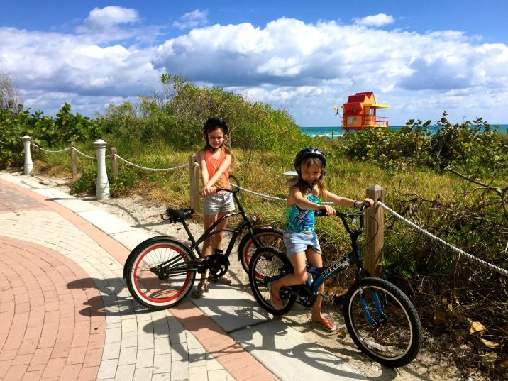 Kids exploring the Boardwalk in South Beach Miami with bikes