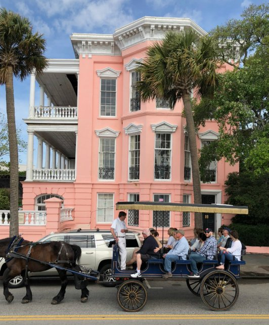 Pink mansion with horse drawn carriage in Charleston