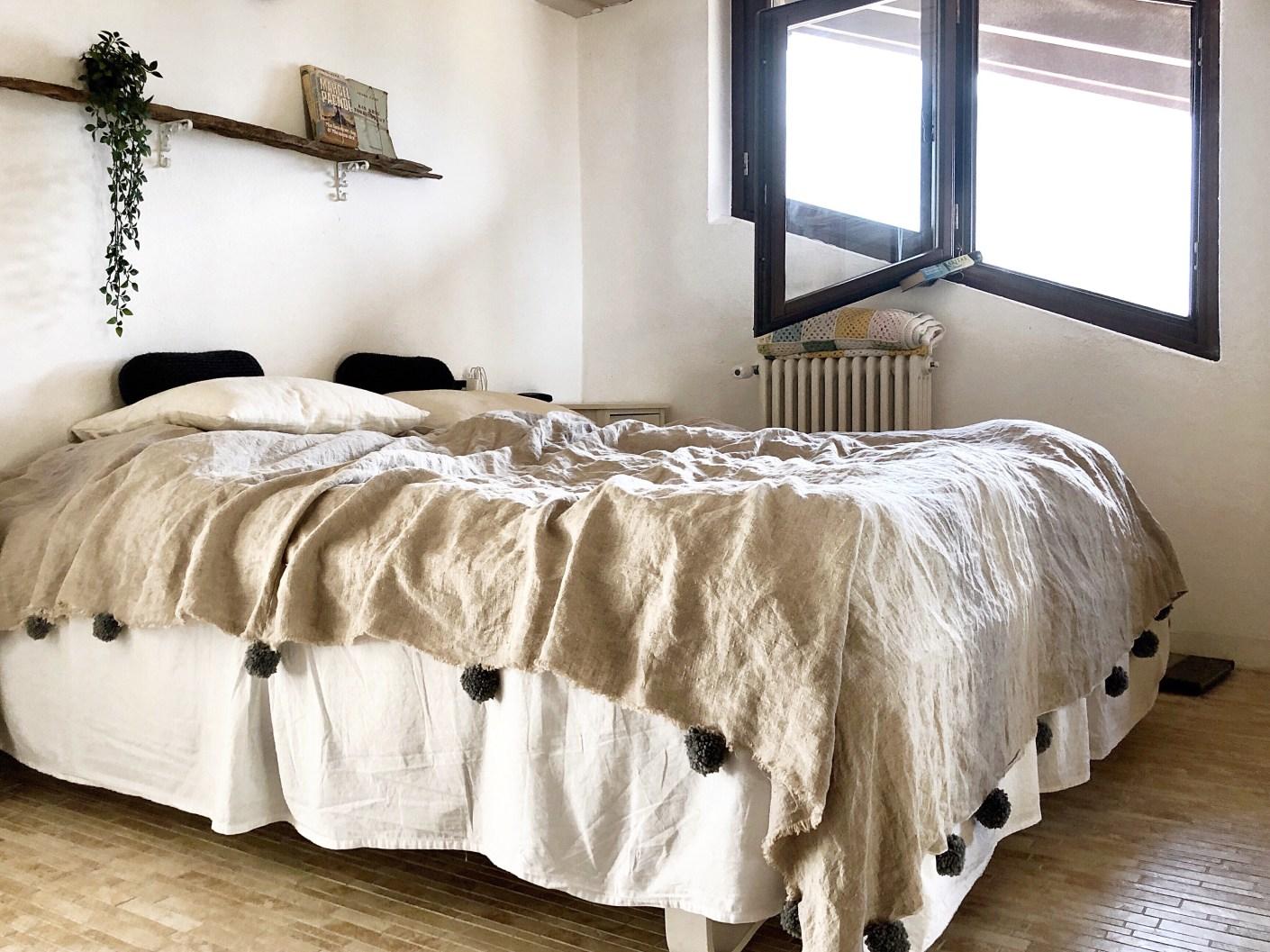 sengetæppe med pom-pomer