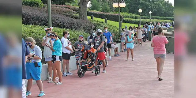Guests in protective masks wait to pick up their tickets at the Magic Kingdom theme park at Walt Disney World on the Florida theme park's reopening day, July 11, 2020.(GREGG NEWTON/Gregg Newton/AFP via Getty Images)