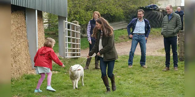 Catherine, Duchess of Cambridge and farmer's daughter Clover Chapman, 9, walk a lamb together, watched by her parents and Prince William, Duke of Cambridge, during a royal visit to Manor Farm in Little Stainton, Durham on April 27, 2021, in Darlington, England.
