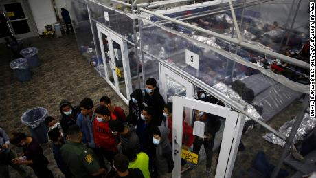 Young minors talk to an agent at the Donna Department of Homeland Security holding facility in the Rio Grande Valley, March 30, 2021.