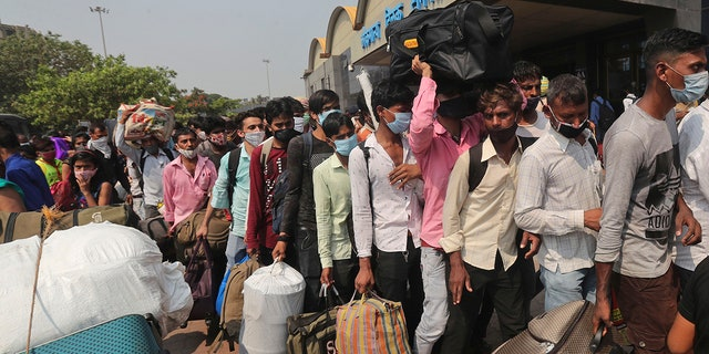 April 14, 2021: People wearing masks as a precaution against the coronavirus stand in queues to board trains at Lokmanya Tilak Terminus in Mumbai.