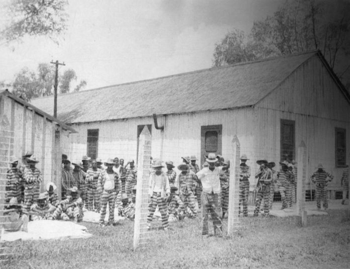 Bluesman Huddie Ledbetter, known as Leadbelly, standing in the foreground at prison compound No 1. in the Louisiana State Pen