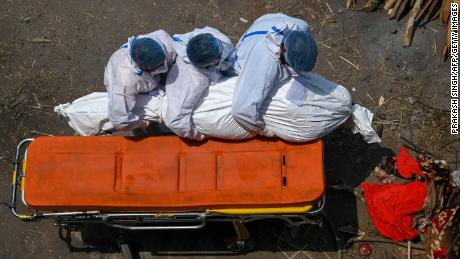 Family members and ambulance workers in protective equipment carry the body of a victim who died of the Covid-19 coronavirus at a cremation ground in New Delhi on April 27, 2021.