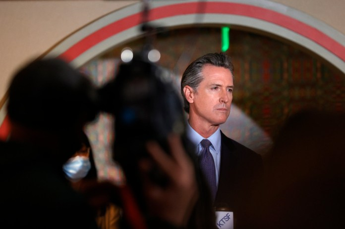 California Gov. Gavin Newsom looks on during a news conference.