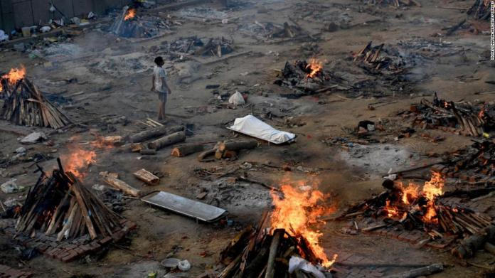 A man stands amid burning pyres of Covid-19 victims at a crematorium in New Delhi, India, on April 26.