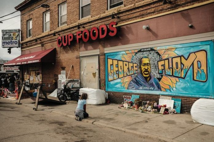 A woman pays respect to a mural of George Floyd by the Cup Foods where he was killed by Minneapolis police officer Derek Chau