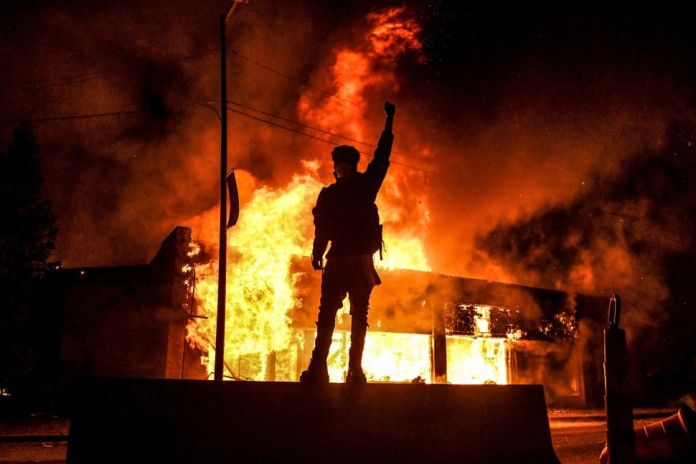 A protester stands in front of a burning building in Minneapolis on May 29, 2020, after the murder of George Floyd.