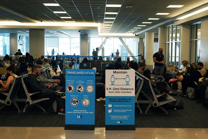 A face mask and social distance advisory sign at the Los Angeles International Airport, Friday, April 9.