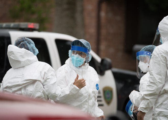 Emergency personnel don PPE before entering the home where more than 90 undocumented immigrants were found on the 12200 block of Chessington Drive, Friday, April 30, 2021, in Houston. A Houston Police official said the case will be handled by federal authorities and that some of the people inside the house were exhibiting COVID-19 symptoms.
