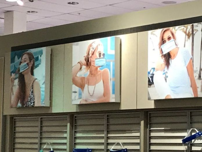 Masks were placed over old photos of fashion models at the abandoned JCPenney where Udi Greenberg received a vaccine.