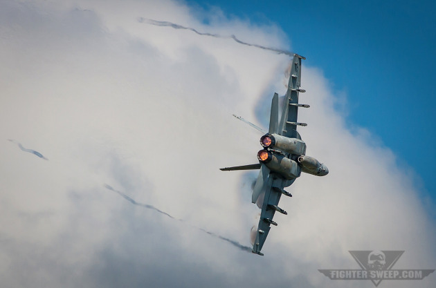An F/A-18E Super Hornet pulls through a high-G turn during a simulated dogfight for the airshow crowd at NAS Oceana, Virginia.