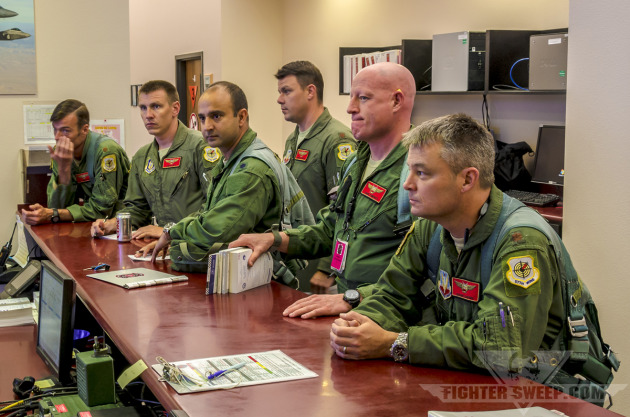 Pilots from the 64th Aggressor Squadron receive their step briefing prior to launch for a night training mission during Red Flag.