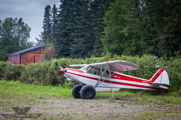 A Super Cub sits at the old Talkeenta Strip, with the former Talkeetna Air Service hangar in the background