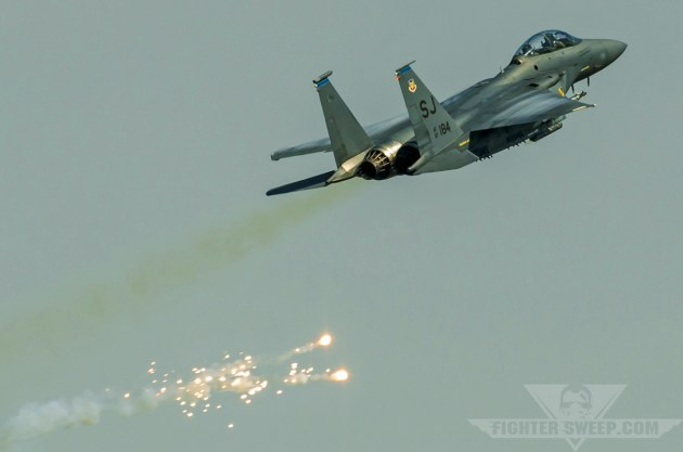 A Boeing F-15E Strike Eagle passes through the target area and dispenses flares to defeat a simulated, ground-based IR missile threat.